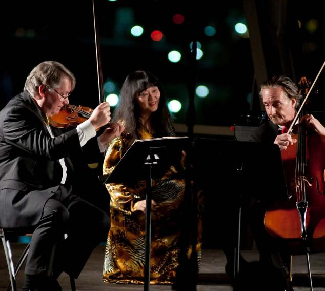 David Finckel, Wu Han, and Philip Setzer playing instruments outdoors at night.